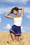 Junge Frau auf einem goldenen Gebiet des Weizens Stockfoto