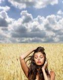 Junge Frau auf einem goldenen Gebiet des Weizens Stockfotografie