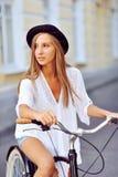 Junge Frau auf einem Porträt des Fahrrades im Freien Stockbild