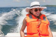 Junge Frau auf einem Schnellboot in einer Schwimmweste auf einer schäumenden Spur des Hintergrundes des Bootes Lizenzfreies Stockbild