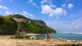 Junge Frau auf einem Strand mit großem Wellen Melasti-Strand auf der Bali-Insel, Indonesien stock video footage