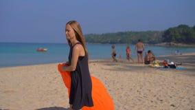 Junge Frau auf einem tropischen Strand ein aufblasbares Sofa aufblasen Reisenkoffer mit Meerblick nach innen stock video