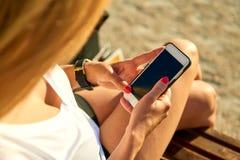 Junge Frau auf einer Bank und der Anwendung ihres Telefons Stockbilder