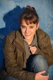 Junge Frau auf einer blauen Wand Stockbild