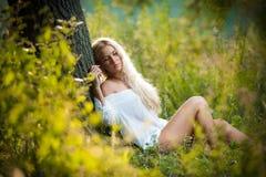 Junge Frau auf Feld im weißen Kleid Stockfotografie