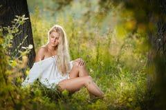 Junge Frau auf Feld im weißen Kleid Stockfotos