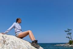 Junge Frau auf großem Felsen gegen blauen Himmel Stockbild