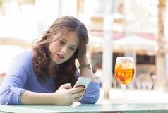 Junge Frau auf ihrem Bruch eine Textnachricht auf dem Mobile lesend stockfotografie