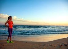 Junge Frau auf Küste bei dem Sonnenuntergang, der Abstand untersucht Stockbild