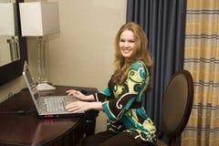 Junge Frau auf Laptop-Computer Lizenzfreie Stockfotos
