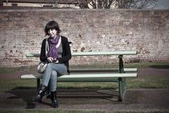 Junge Frau auf Parkbank. Stockbild