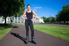 Junge Frau auf Rollschuhen im Sommerpark stockbild