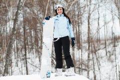 Junge Frau auf Snowboard stockbilder