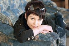 Junge Frau auf Sofa Stockbilder