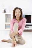 Junge Frau auf Wohnzimmerfußboden Lizenzfreies Stockbild