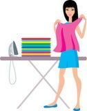 Junge Frau bügelt Kleidung Stockbild