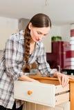 Junge Frau baut einen Schrank zusammen Lizenzfreies Stockbild
