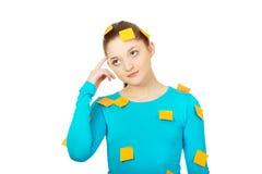 Junge Frau bedeckt mit Post-Itanmerkungen Stockbild