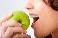Junge Frau beißt in einem frischen und gesunden Apfel Lizenzfreie Stockfotos