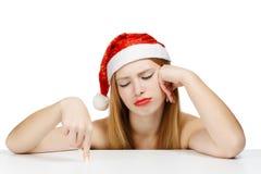 Junge Frau bei der Weihnachtsmann-Hutaufstellung lokalisiert auf weißem backgrou Stockfotografie