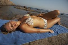 Junge Frau beim Bikinilügen Stockbild