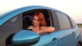 Junge Frau benutzt einen Handy in ihrem Auto stock video footage