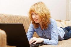 Junge Frau benutzt einen Laptop Stockfotos