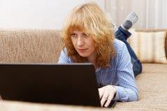 Junge Frau benutzt einen Laptop Lizenzfreie Stockfotografie
