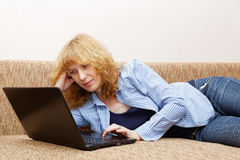 Junge Frau benutzt einen Laptop Stockfoto