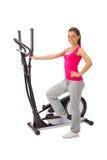 Junge Frau benutzt elliptischen Cross-Trainer. Stockfoto