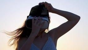 Junge Frau benutzt Gläser einer virtuellen Realität auf dem Strand Sexy Mädchen, das Erfahrung erhält, wenn an VR-Kopfhörer am So stock footage