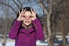 Junge Frau beobachtet im Feldglas, das von den Fingern der Hände gemacht wird Lizenzfreie Stockbilder