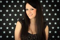 Junge Frau über dunklem Hintergrund mit weißen Sternen Stockfoto