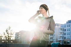 Junge Frau bereit Training zum im Freien, das durch Musik hört Stockfotografie
