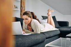Junge Frau beschäftigt unter Verwendung eines Laptops zu Hause Lizenzfreie Stockfotografie