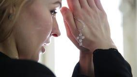 Junge Frau betet weibliche Hände der Nahaufnahme halten Ketten mit einem Kreuz stock video footage