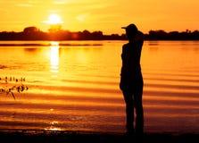 Junge Frau betrachtet in den Abstand, der auf jemand Sonnenuntergang wartet Lizenzfreie Stockfotos