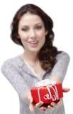 Junge Frau bietet ein Geschenk an Stockfoto