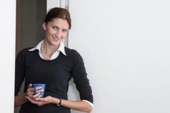 Junge Frau bildet eine Kaffeepause Lizenzfreie Stockbilder