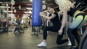 Junge Frau bildet mit persönlichem Trainer im Sportverein aus stock footage