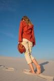 Junge Frau, blond in einem Leuchtorangehemd auf dem Strand Stockbild