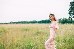 Junge Frau in Boho-Kleid, das auf Wiese steht Stockfoto