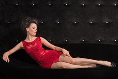 Junge Frau Brunette im roten Kleid, das auf Schwarzes legt Lizenzfreies Stockfoto