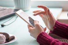 Junge Frau am Café Handy herein trinkend und verwendend Sonntag Morgen Stockbilder