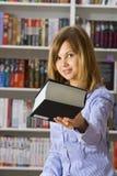 Junge Frau dehnt großes schwarzes Buch aus Stockfotos