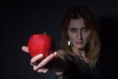 Junge Frau dehnt roten Apfel aus Stockbild