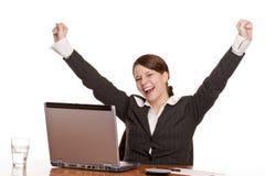 Junge Frau in den Büro jubilates am Schreibtisch Lizenzfreie Stockbilder