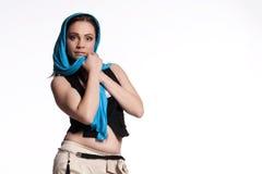 Junge Frau in den beige Hosen, schwarze Weste mit blauem Schal Stockfotografie