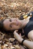 Junge Frau in den Blättern Stockbild