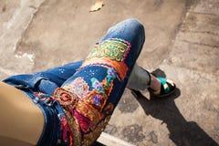 Junge Frau in den Blue Jeans und in den hohen Absätzen in der Hinterhofsommergussnaht lizenzfreies stockbild